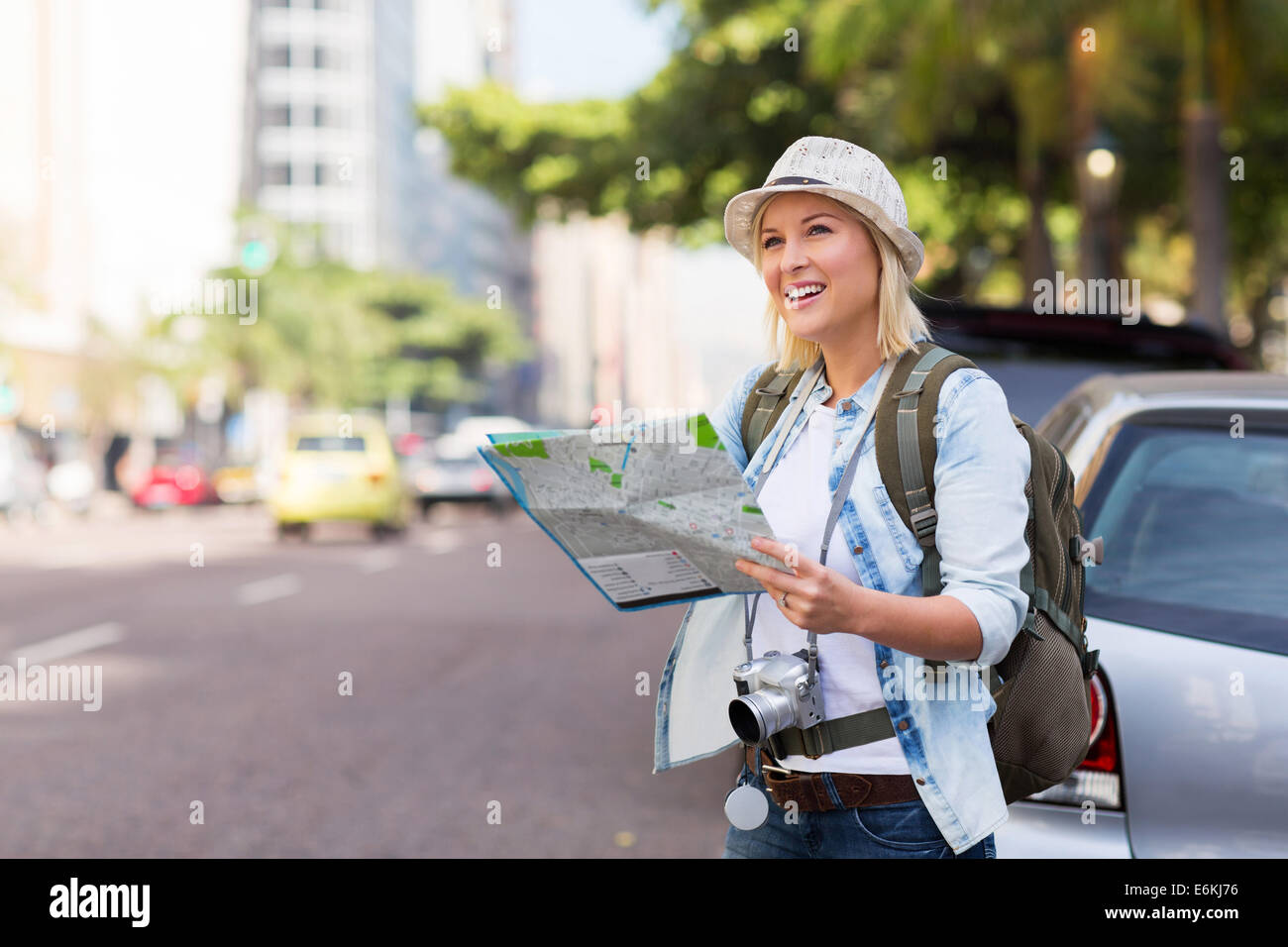 tourist standing on the sidewalk of an urban street with map - Stock Image