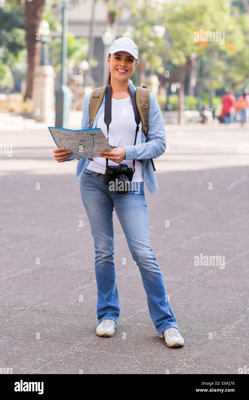 attractive female traveller holding a map in city - Stock Image