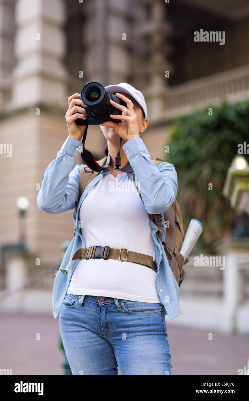 female traveller taking photos using digital camera in the city - Stock Image