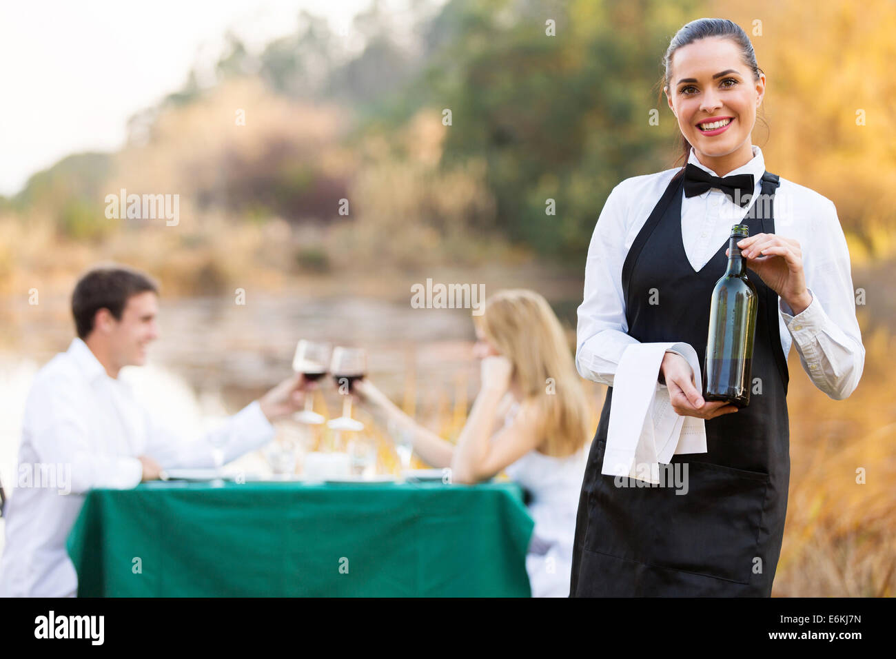 attractive waitress holding a bottle of wine in front of customers - Stock Image