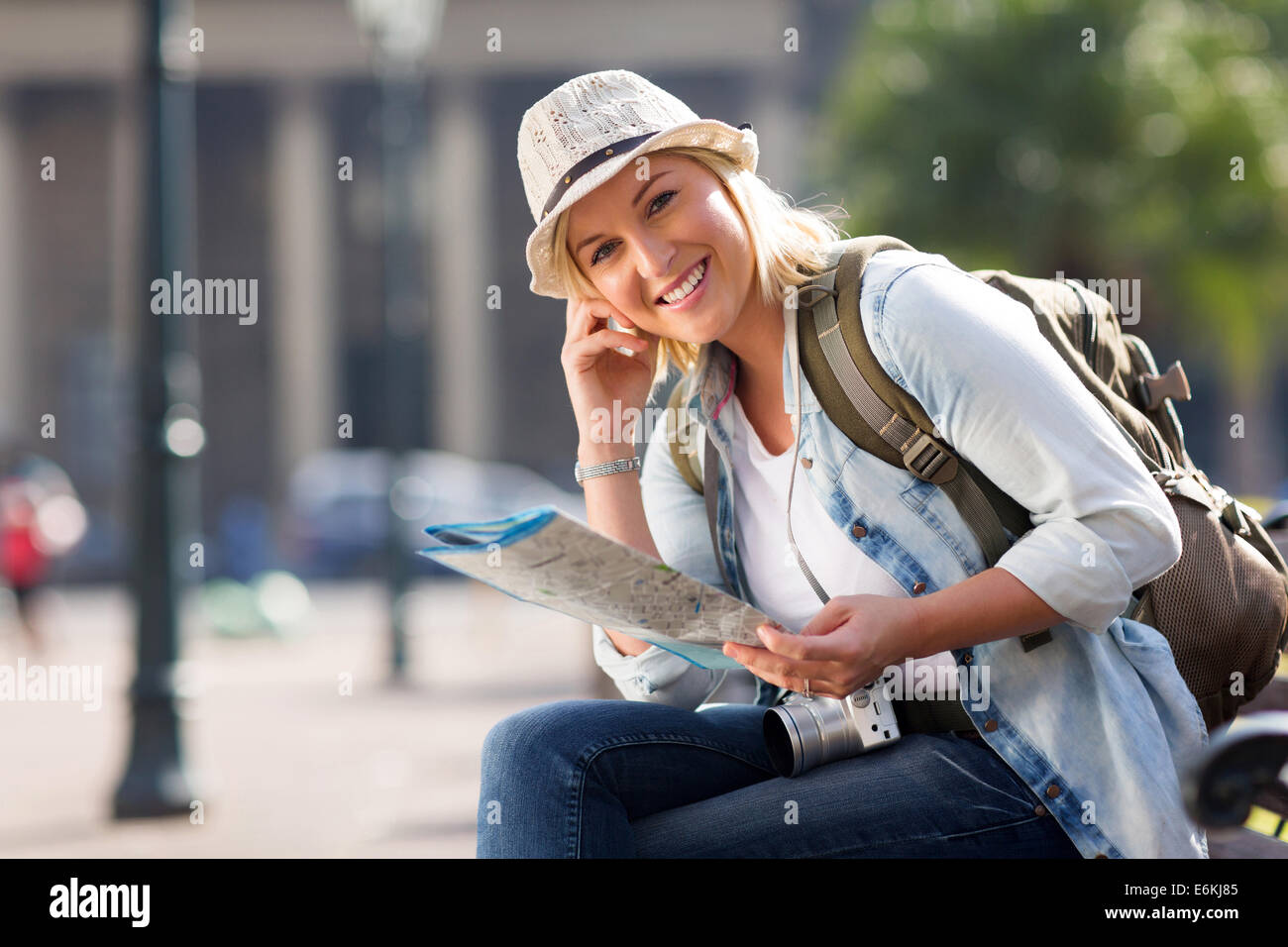 pretty female traveller holding a map and sitting on bench in the city - Stock Image