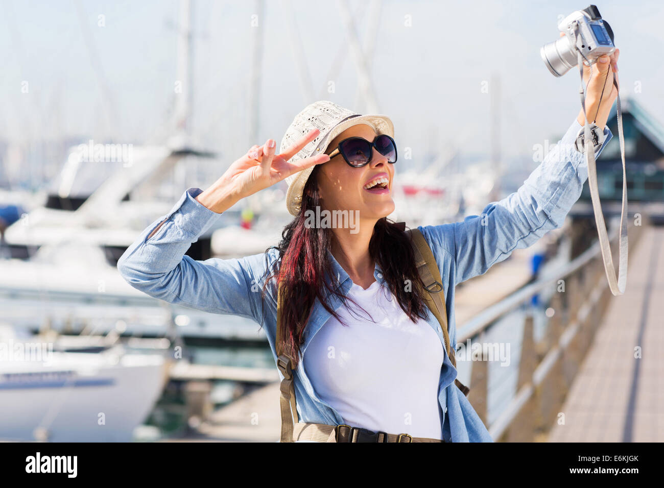 young female traveller taking a selfie by the harbor - Stock Image