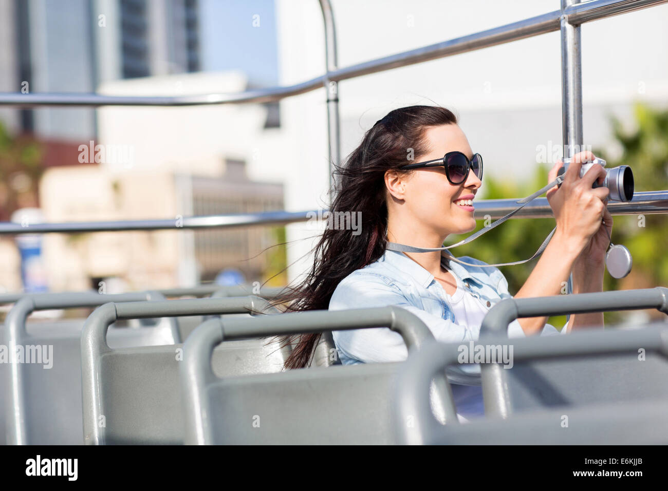 female traveller taking video of the city using digital camera from an open top bus - Stock Image