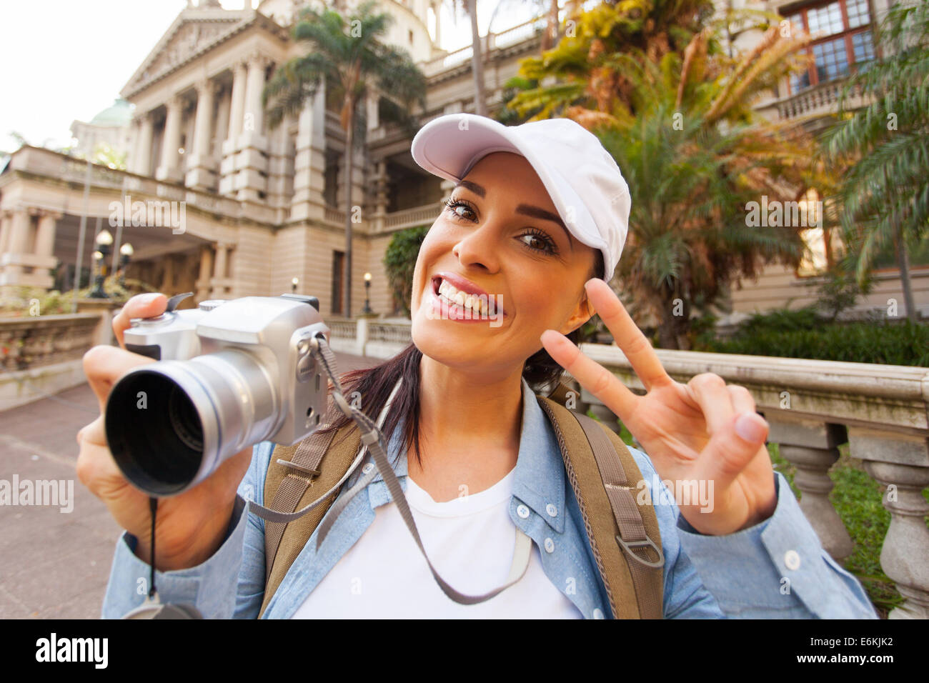 happy young traveller posing in front of an historical building - Stock Image
