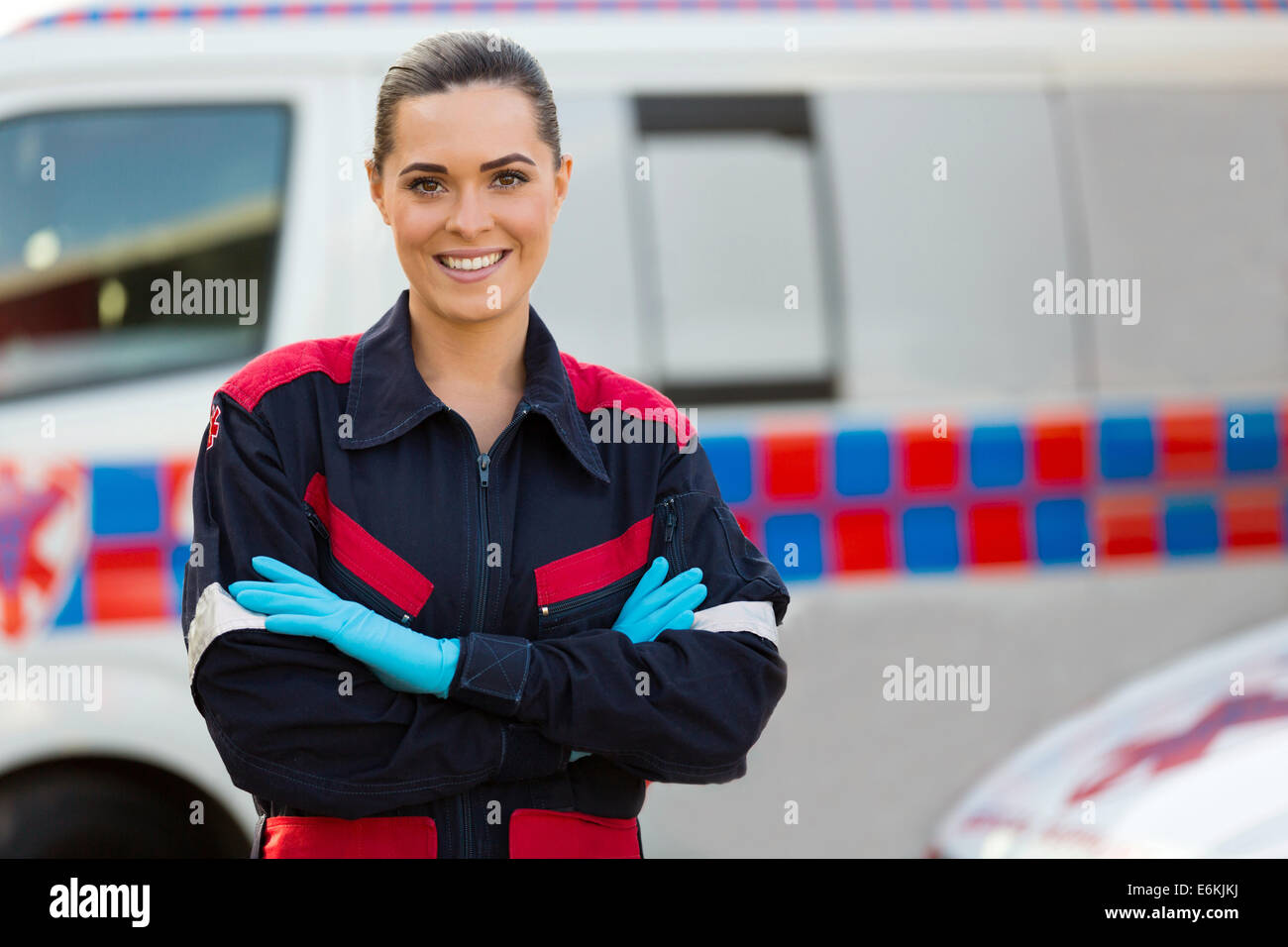 beautiful female paramedic with arms crossed in front of ambulance - Stock Image