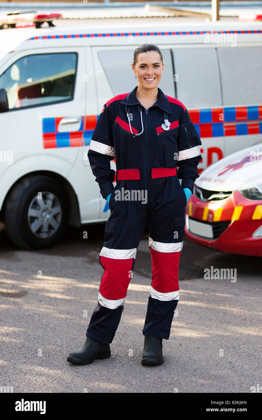 happy emergency medical service worker standing in front of ambulance - Stock Image