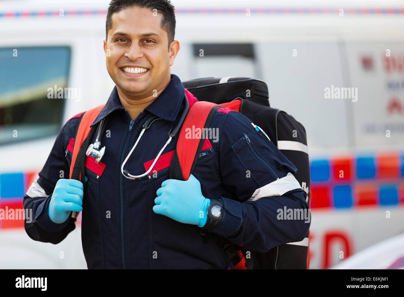 happy emergency medical service staff carrying equipment - Stock Image
