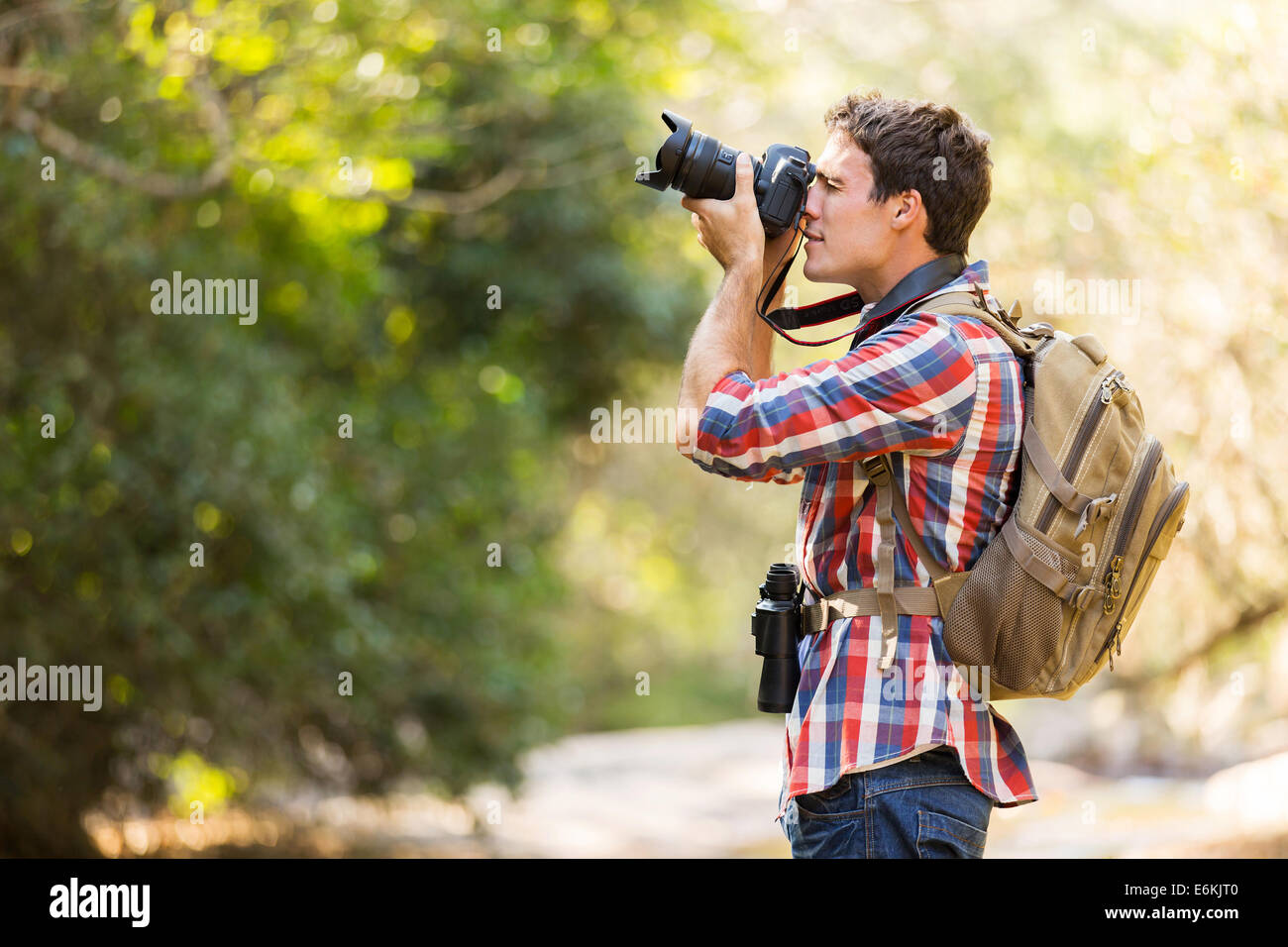 young hiker taking photos in mountain valley - Stock Image
