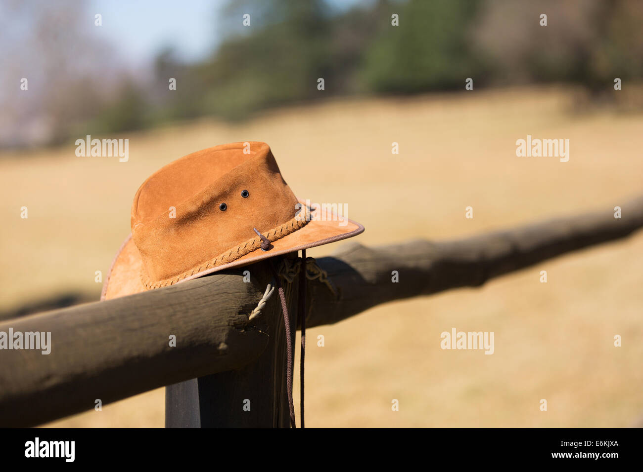 cowboy hat hanging on farm fence - Stock Image