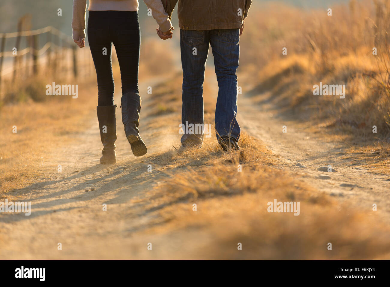 young couple holding hands walking on autumn rural path in the morning - Stock Image