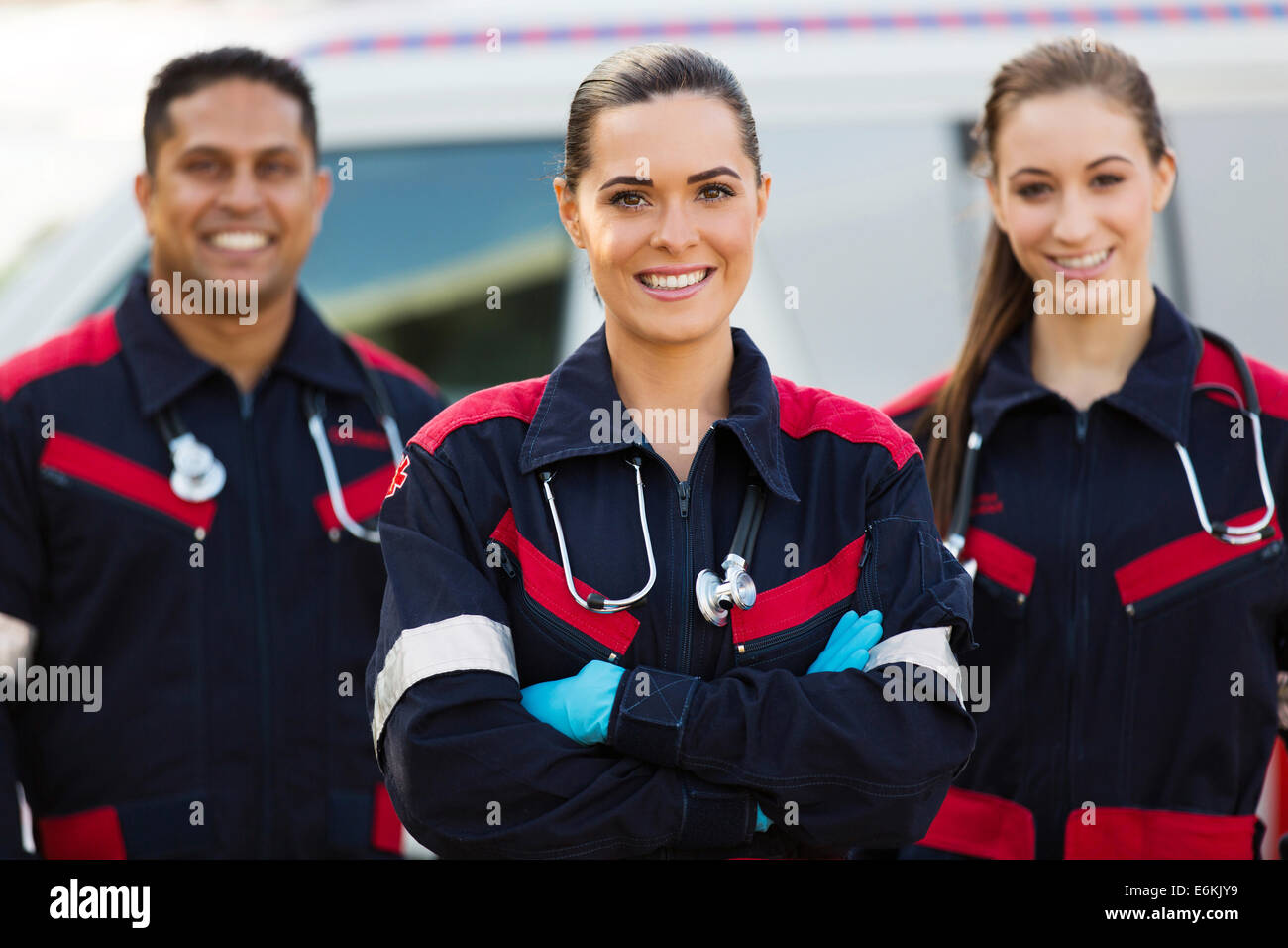 beautiful young EMT with colleagues in front of ambulance - Stock Image