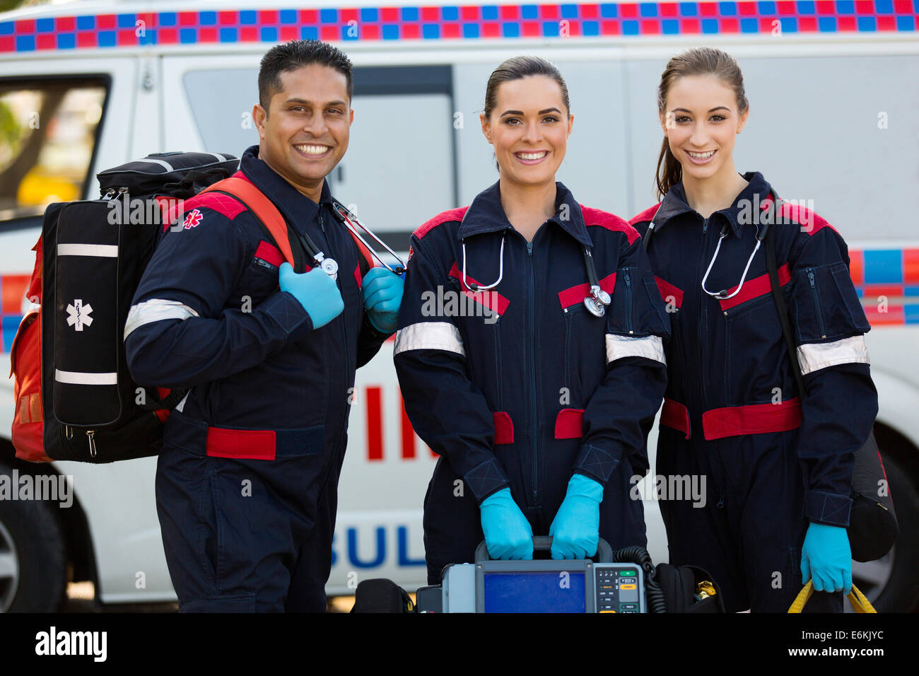 happy paramedics carrying portable equipments in front of ambulance - Stock Image