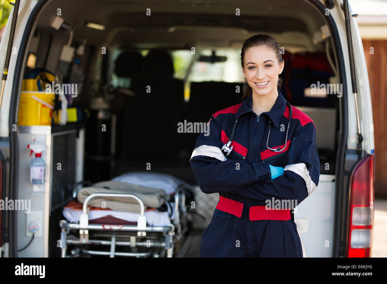 happy female paramedic standing in front of ambulance - Stock Image