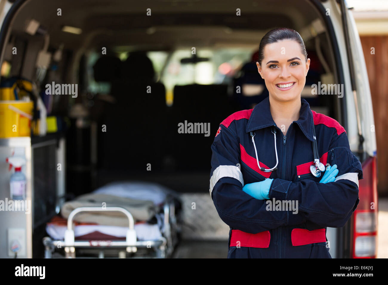 attractive young female emergency medical service worker in front of ambulance Stock Photo