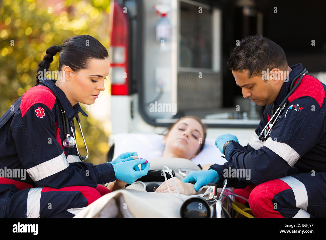 professional paramedics giving unconscious young woman first aid Stock Photo