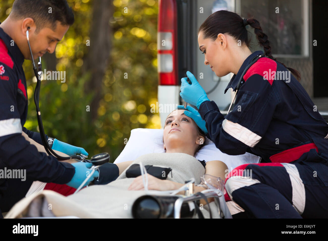 team of emergency medical technicians checking patients vital signs - Stock Image