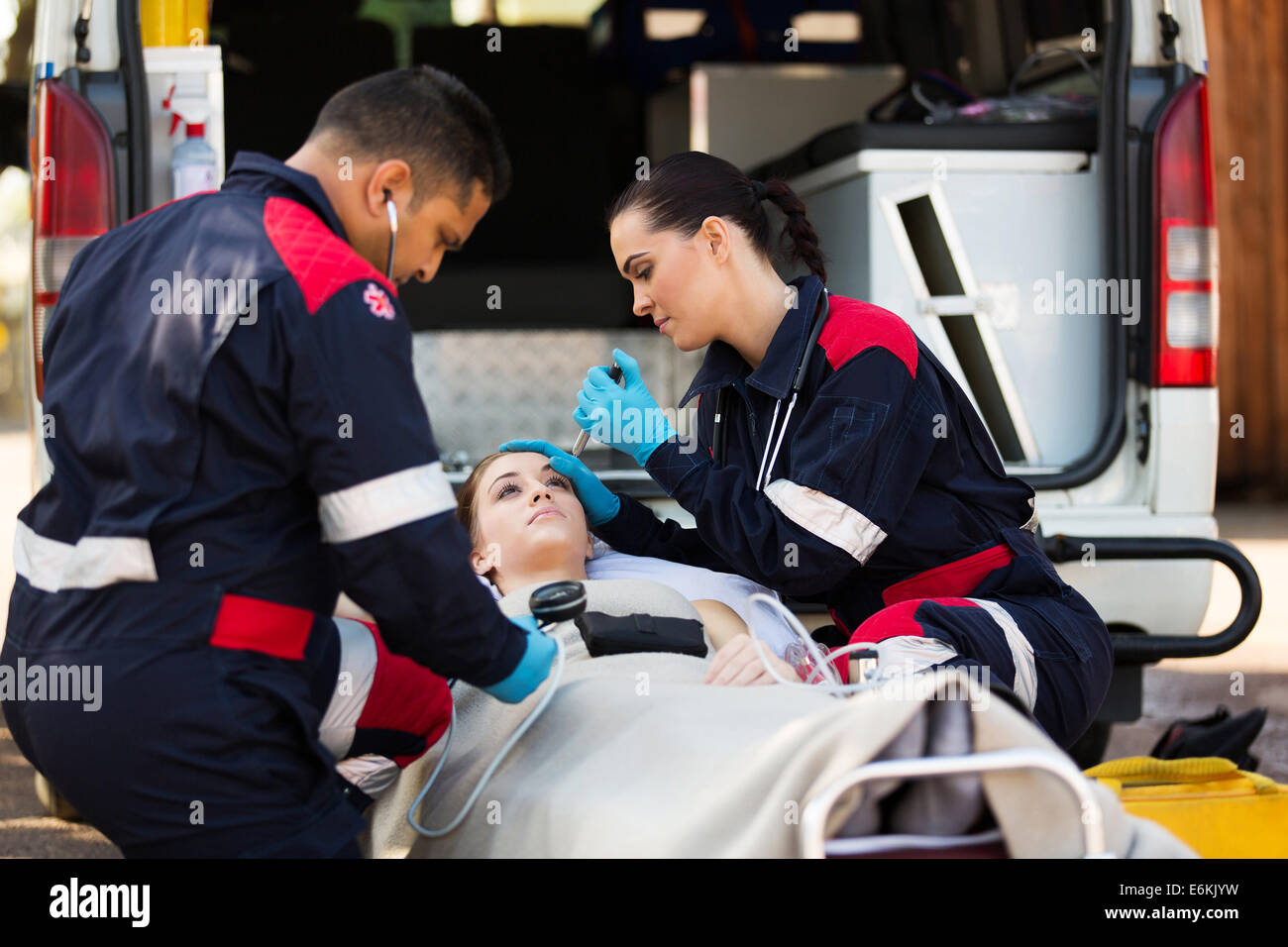 paramedic team examining young female patient - Stock Image