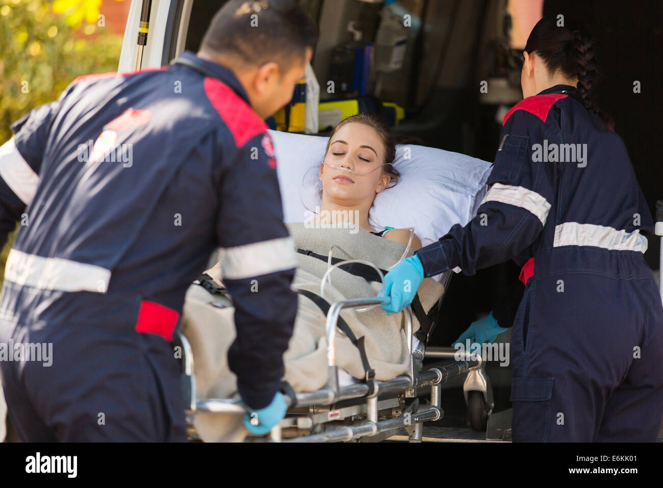 paramedics taking unconscious patient into an ambulance Stock Photo