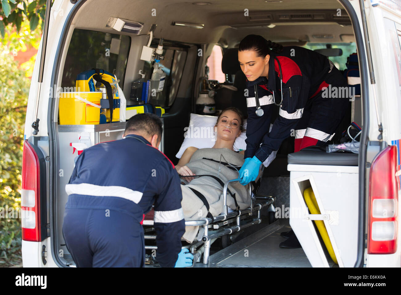 emergency medical staff team transporting patient to hospital with ambulance - Stock Image