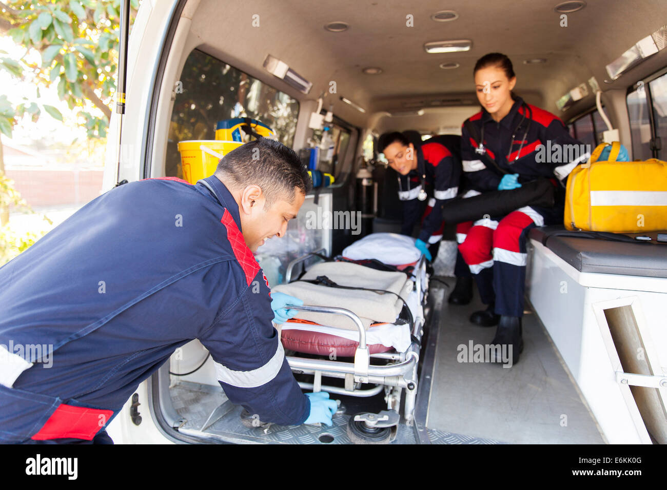 team paramedics taking stretcher out of an ambulance - Stock Image