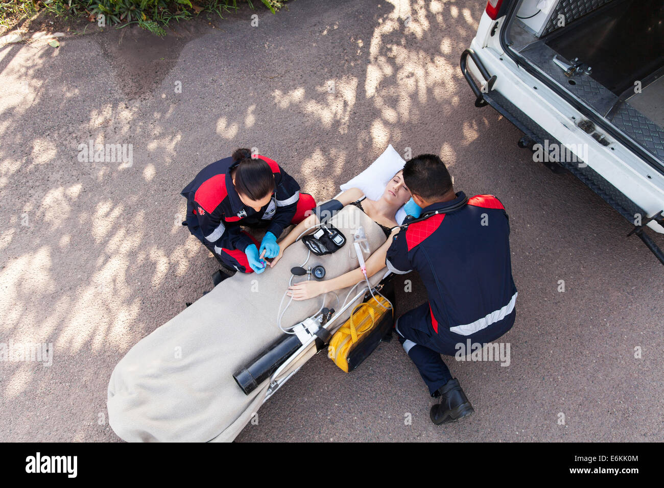 overhead view of paramedic team providing first aid to unconscious woman Stock Photo