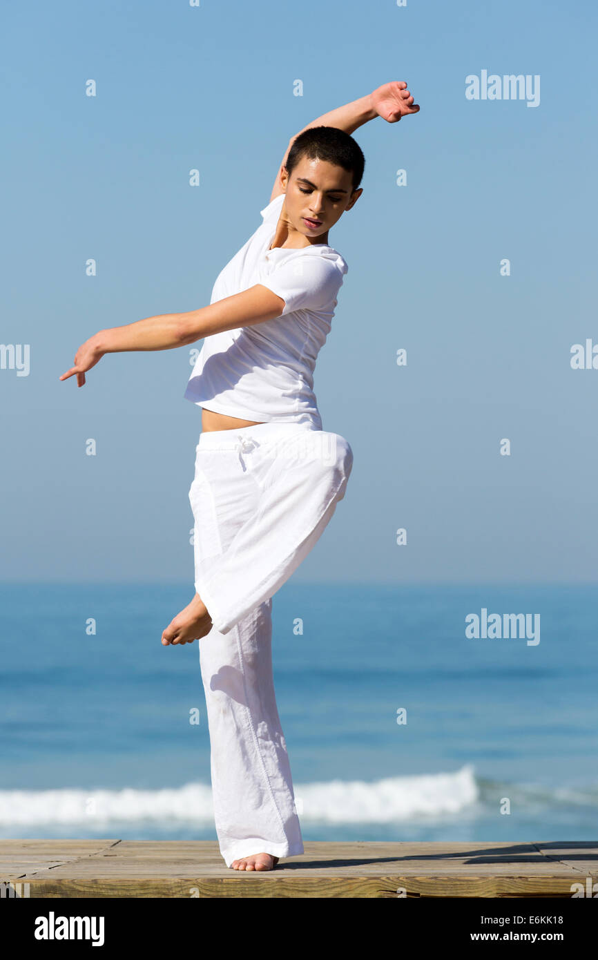 portrait of professional dancer dancing on beach - Stock Image