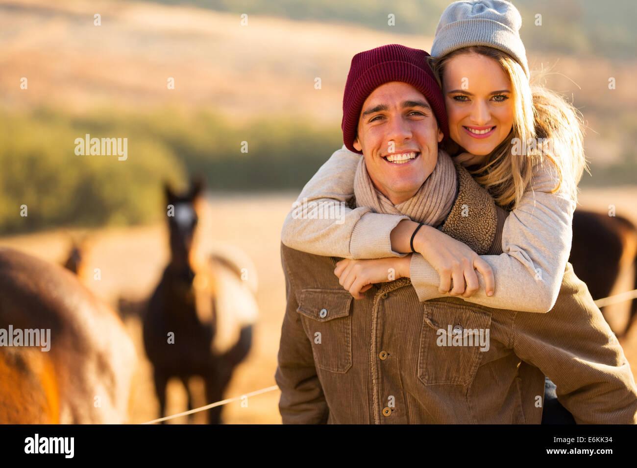 happy woman enjoying piggyback ride on boyfriends back - Stock Image