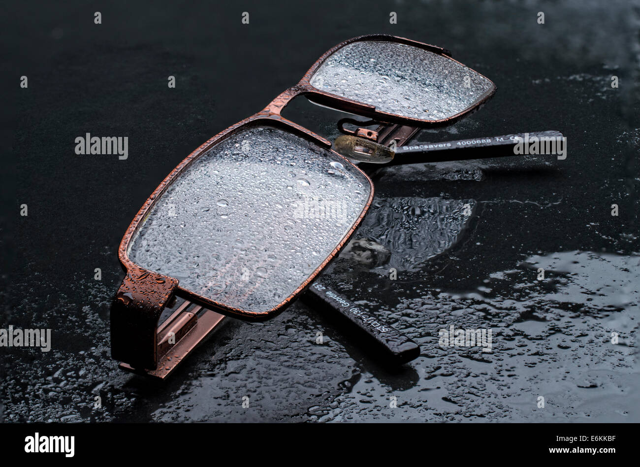 A pair of spectacles spattered with raindrops - Stock Image