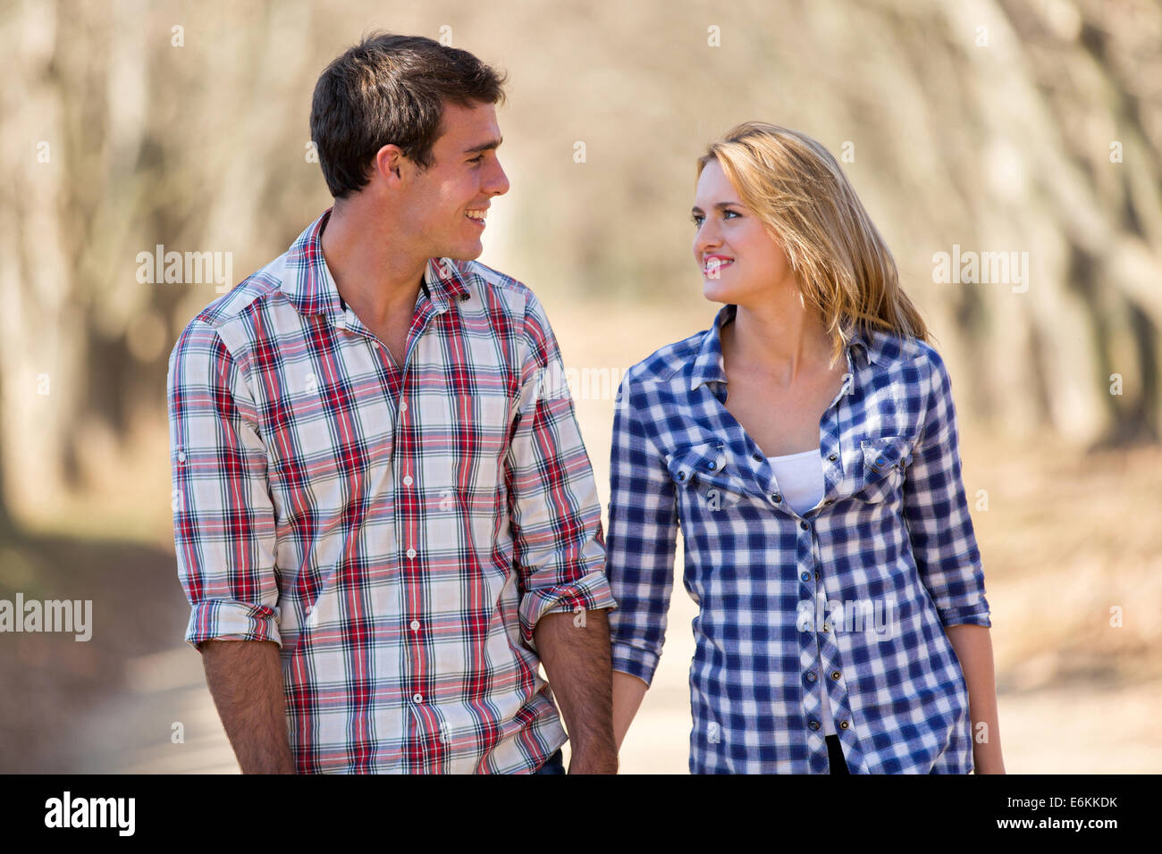 cheerful young couple enjoying a walk in fall - Stock Image