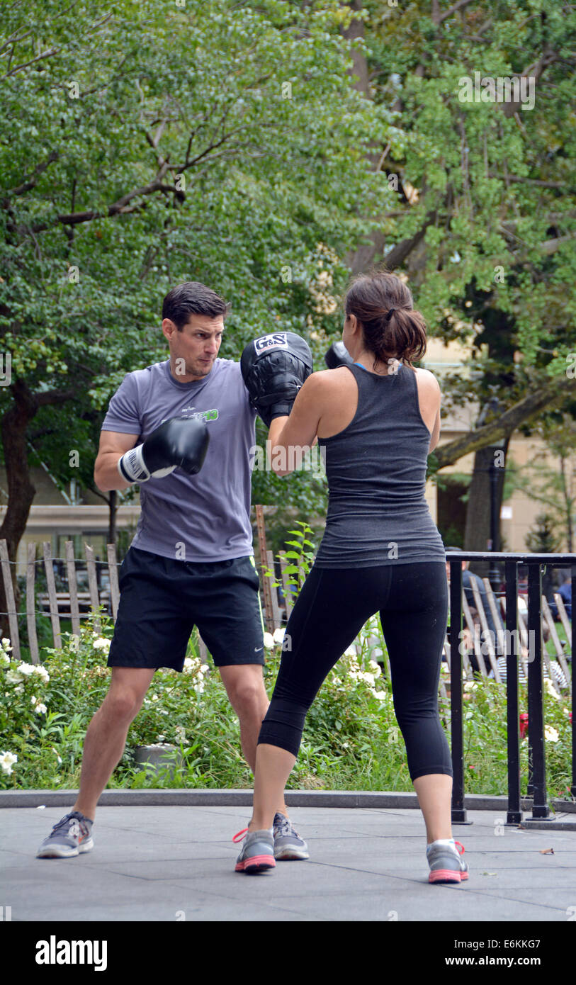 A young man & young woman at a boxing exercise class in Washington Square Park in Greenwich Village, New York - Stock Image