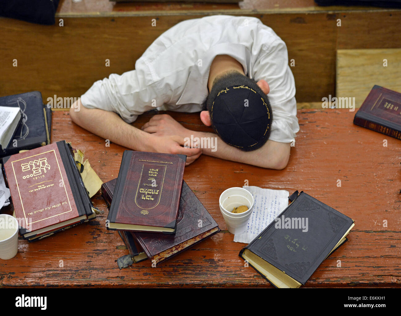 A religious Jewish boy pauses from his studies for thought, contemplation & rest in a synagogue in Brooklyn, - Stock Image
