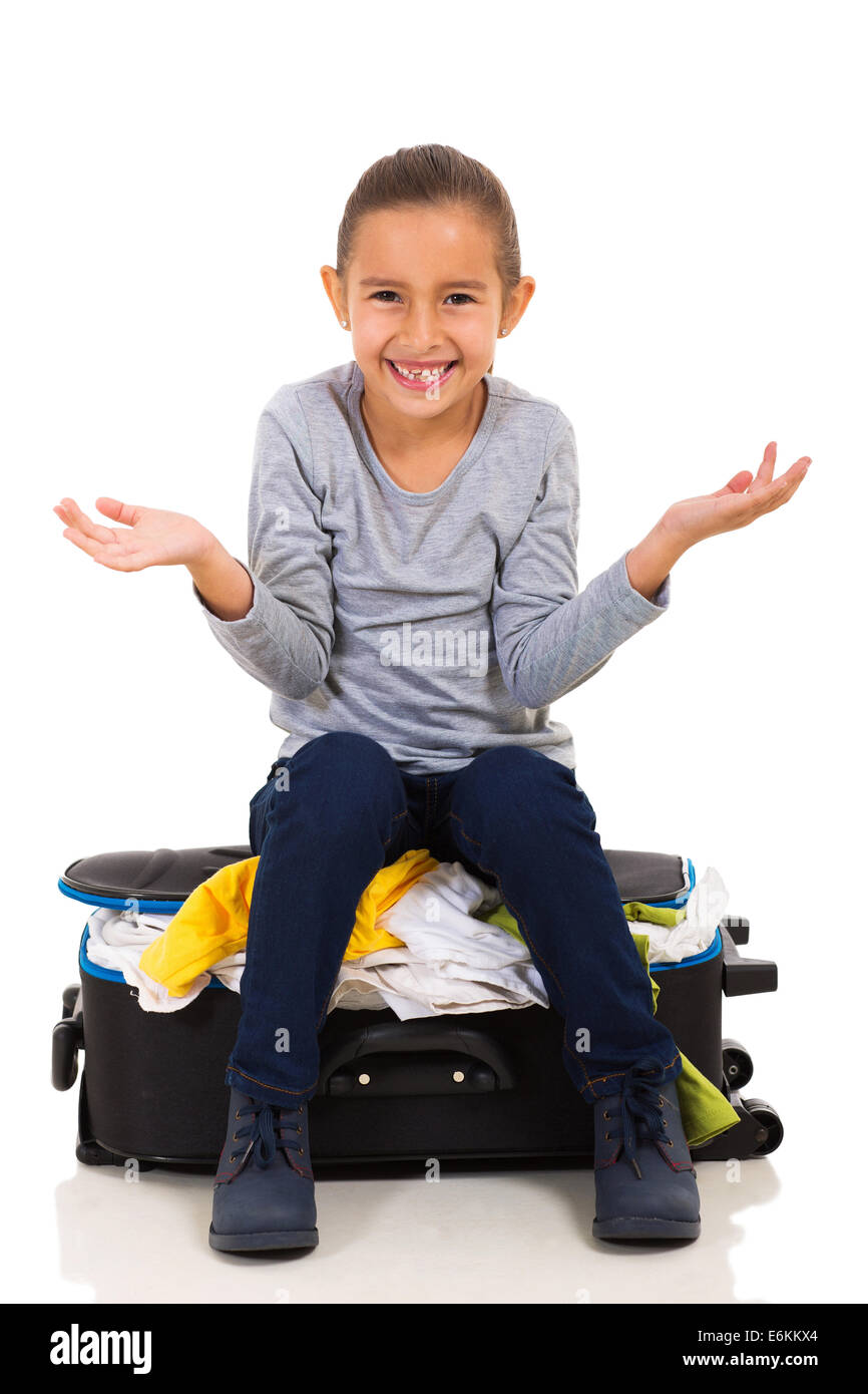 cute little girl sitting on overfilled suitcase Stock Photo