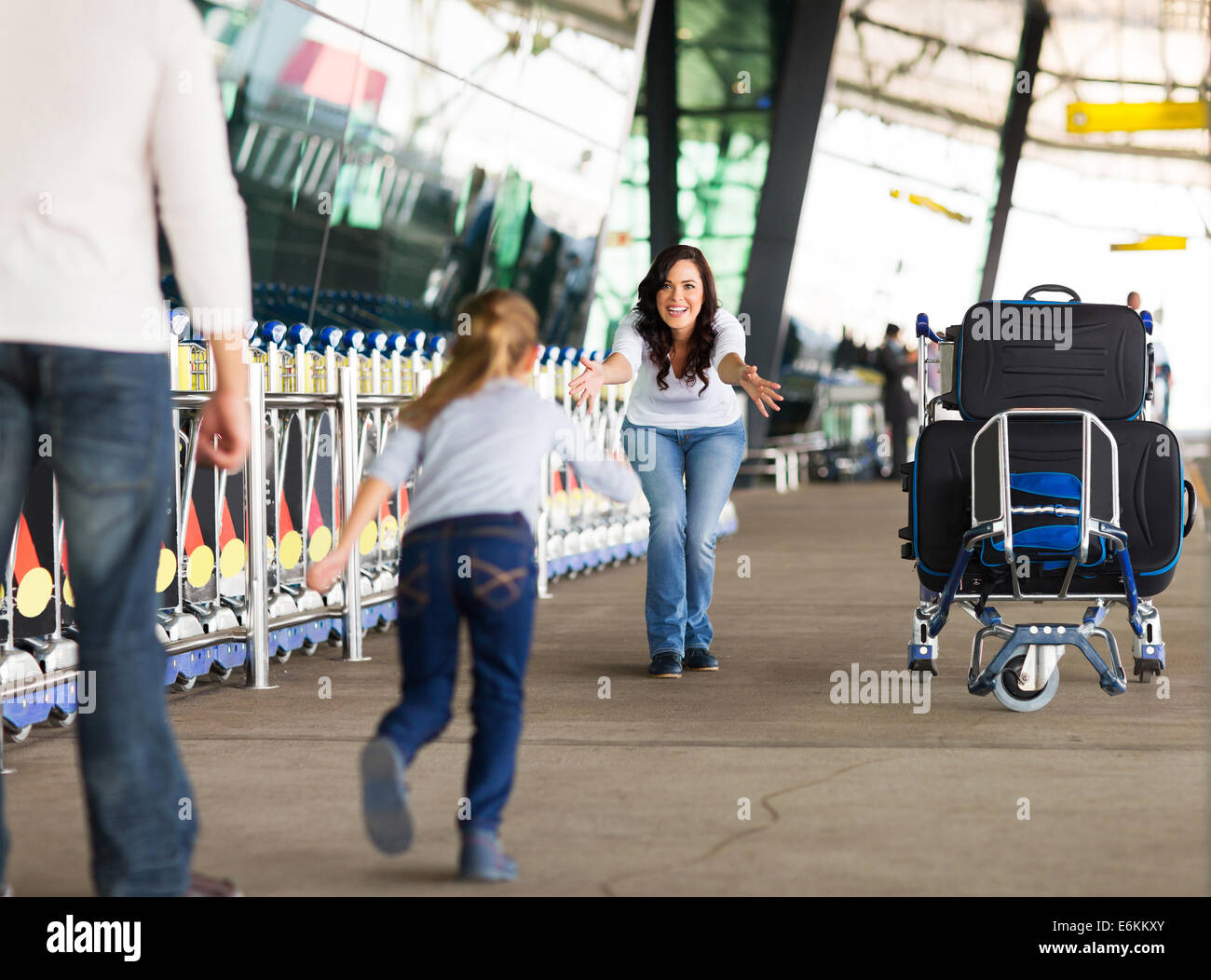 young girl running to her mother at airport after a long wait with her father - Stock Image