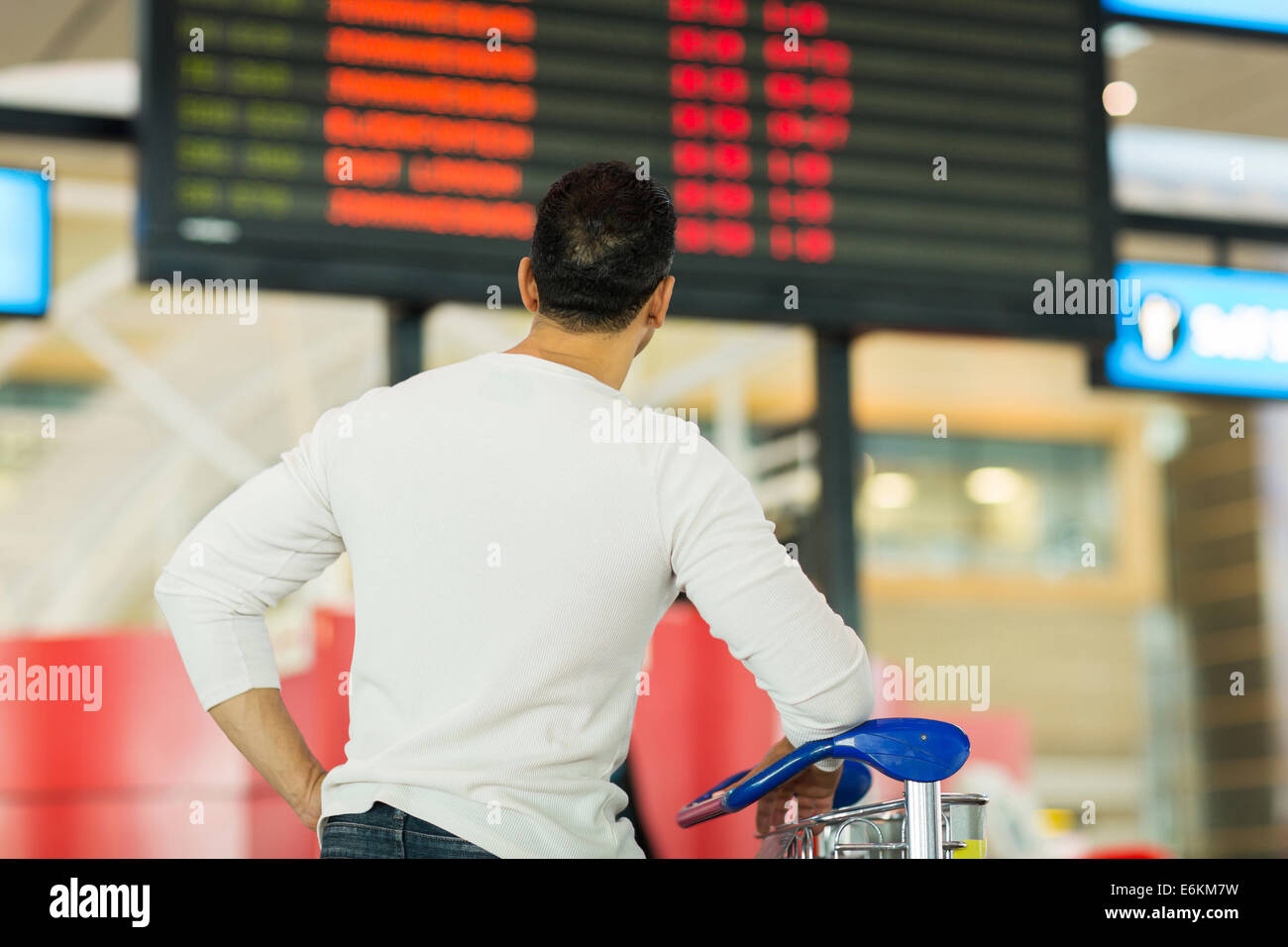 back view of traveller looking at airport information board - Stock Image