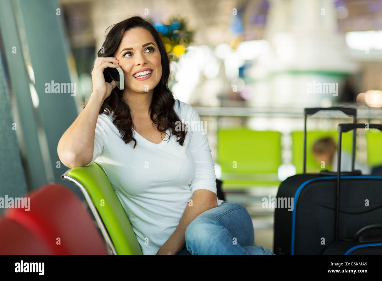 pretty traveller making a phone call at airport - Stock Image