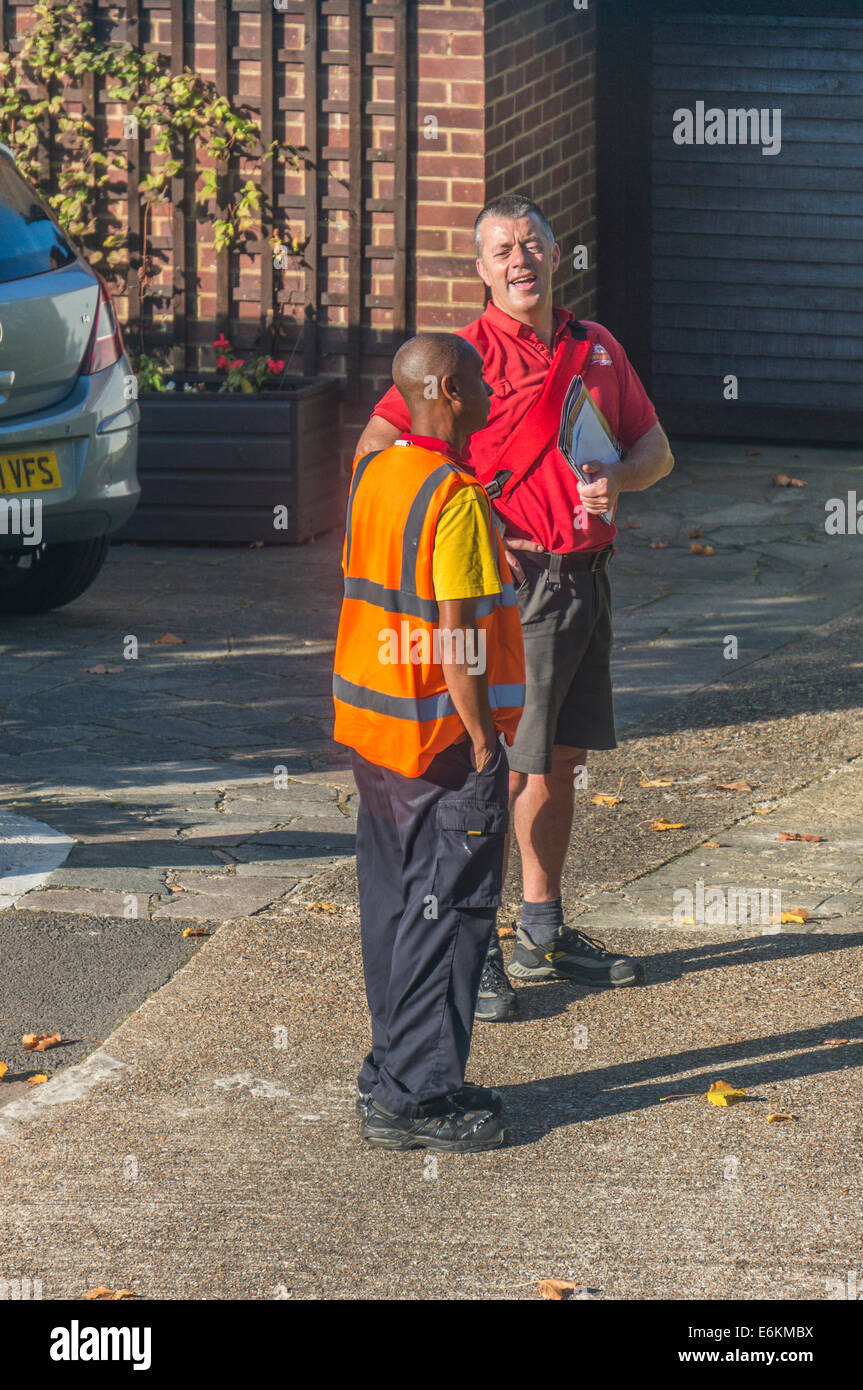 A delivery van driver courier chatting to a happy postman doing his post round in Royal Mail summer shorts uniform. - Stock Image