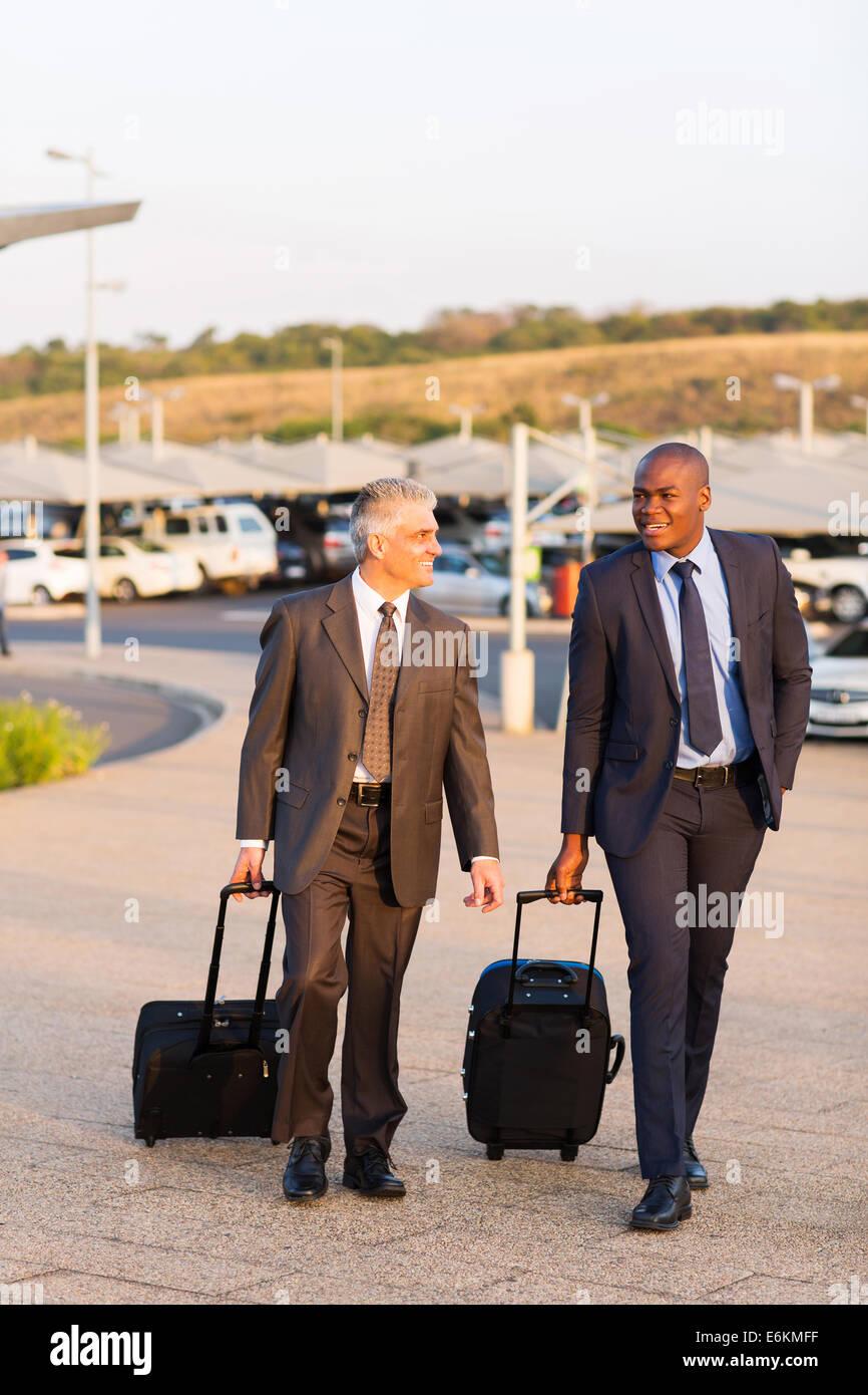 smart businessmen walking in airport parking lot - Stock Image