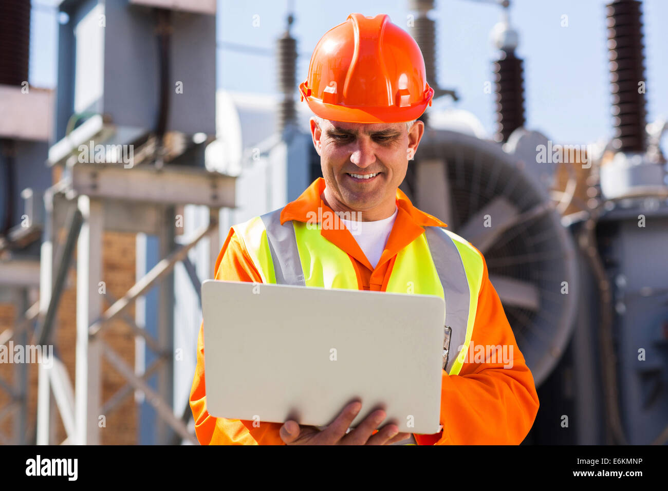 mid age engineer using laptop computer in electricity power plant - Stock Image