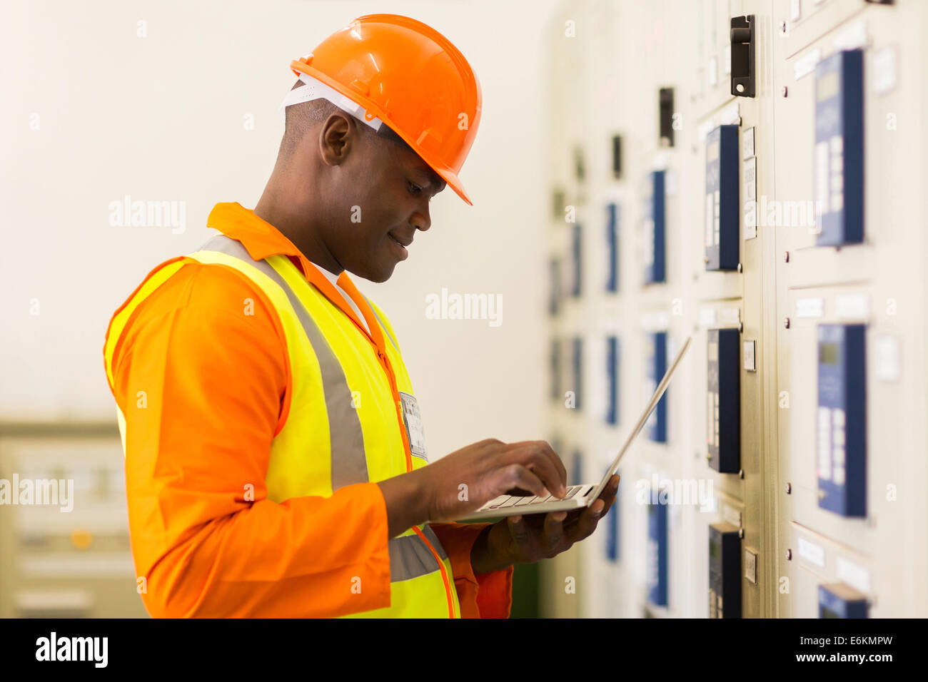 handsome young African control room engineer using laptop - Stock Image