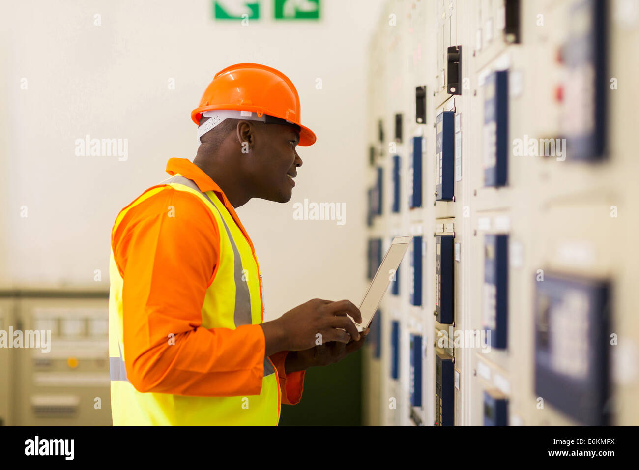 professional African power company technical worker in control room - Stock Image