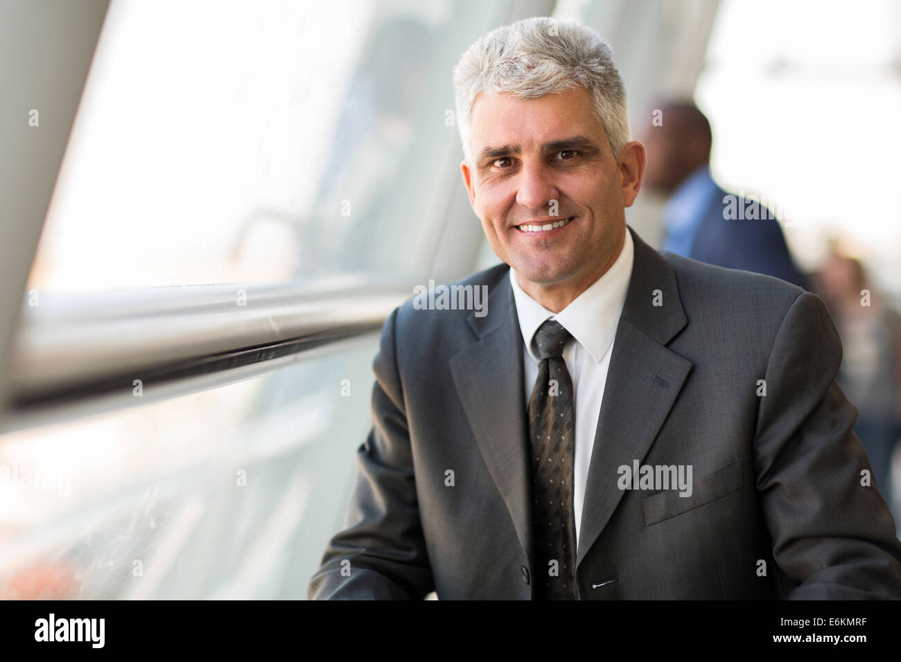 handsome middle aged businessman in modern office - Stock Image