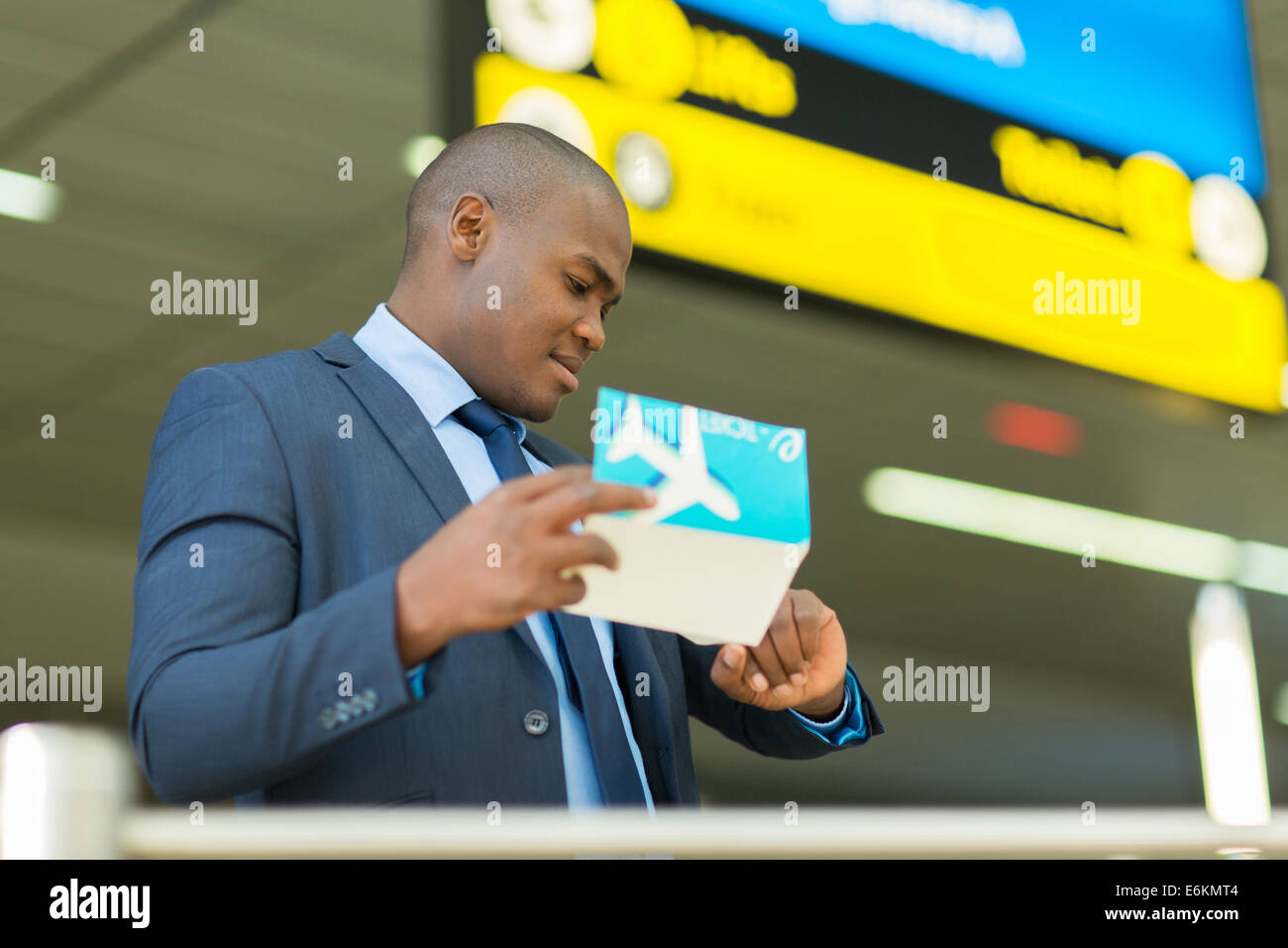 professional African American business traveller checking time at airport - Stock Image