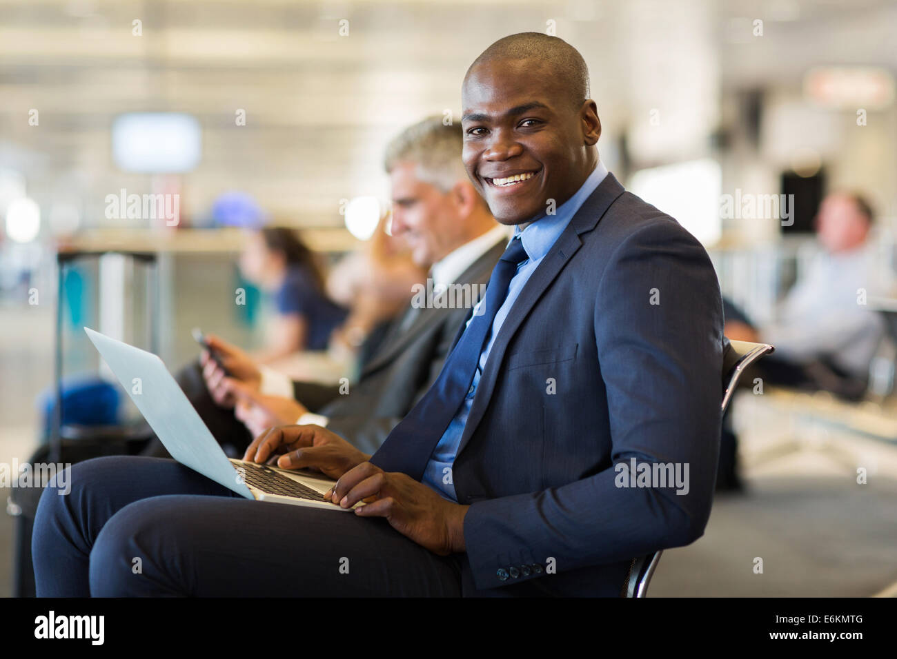 happy African business traveller with laptop computer at airport - Stock Image