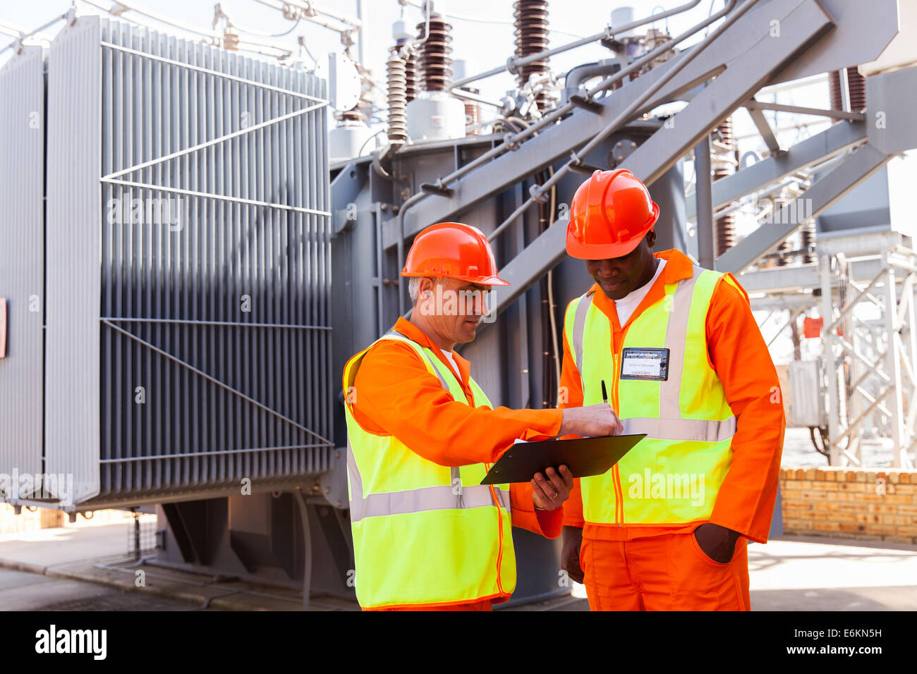 electrical engineers discussing work in power plant Stock
