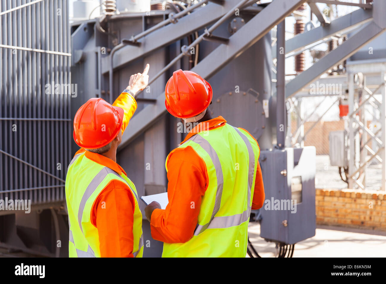 rear view of electrical engineers working in substation Stock Photo
