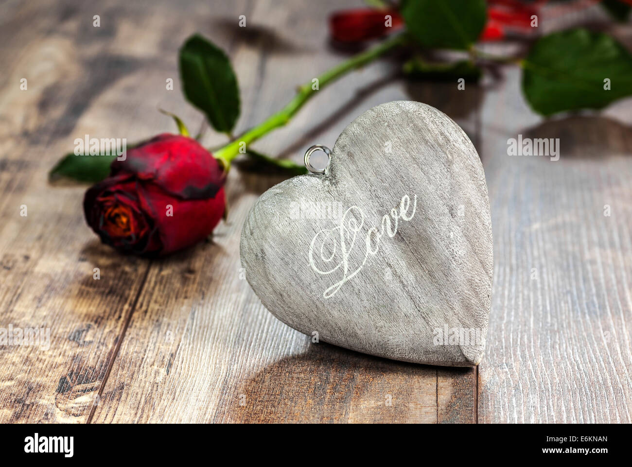 Valentine's day symbol. Heart on a wooden background with red rose. - Stock Image