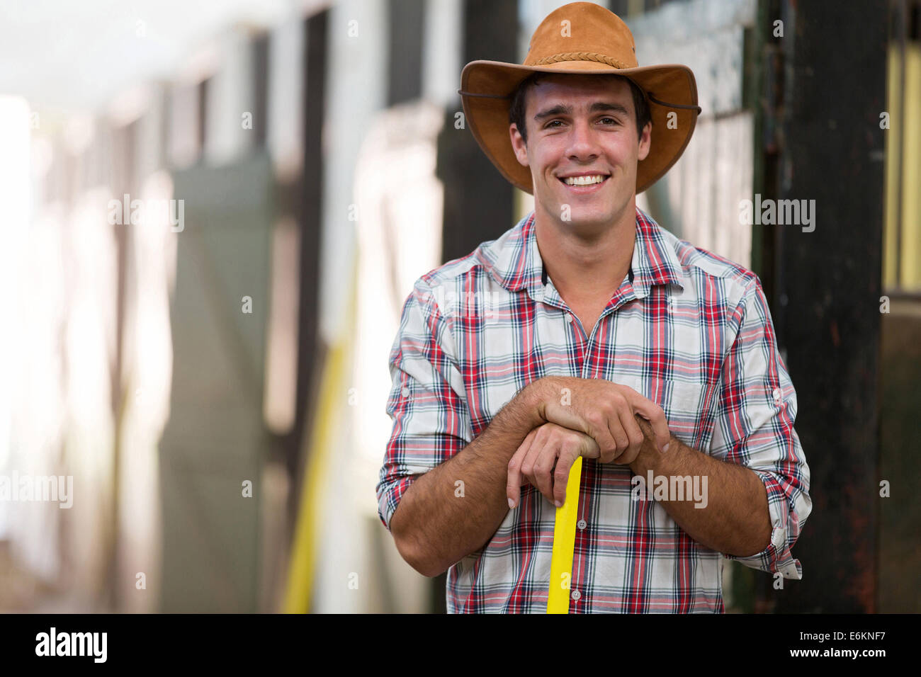portrait of happy horse breeder inside stable - Stock Image