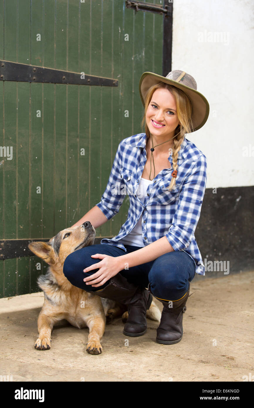 happy country girl and her dog inside farm house - Stock Image