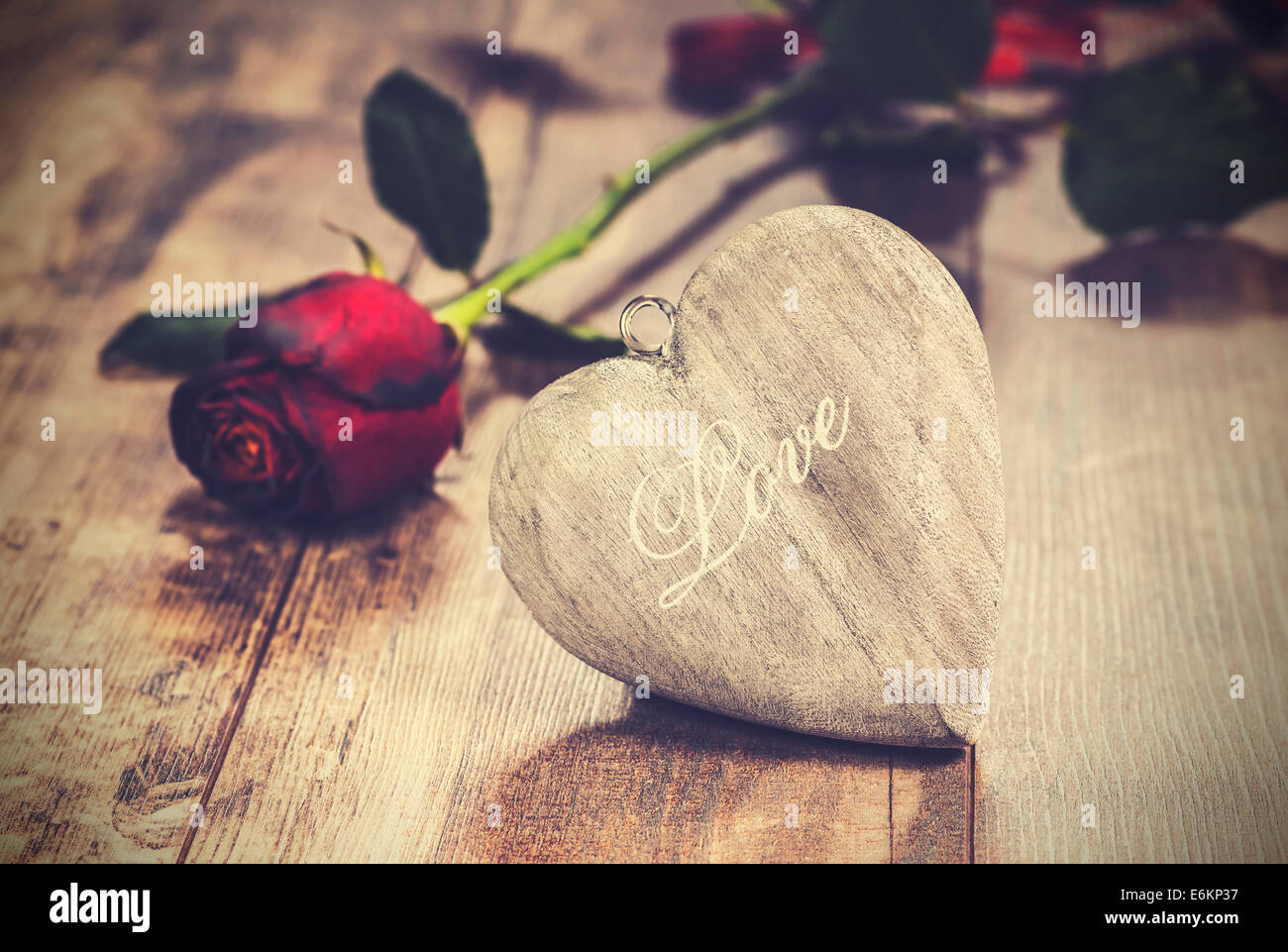 Vintage picture of heart on a wooden background with red rose. Valentine's day symbol. - Stock Image