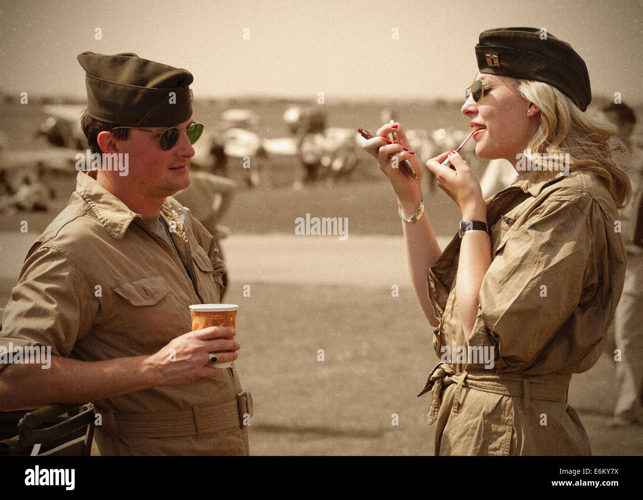 A brief acquaintance as girl is applying her lipstick as the soldier looks on. - Stock Image